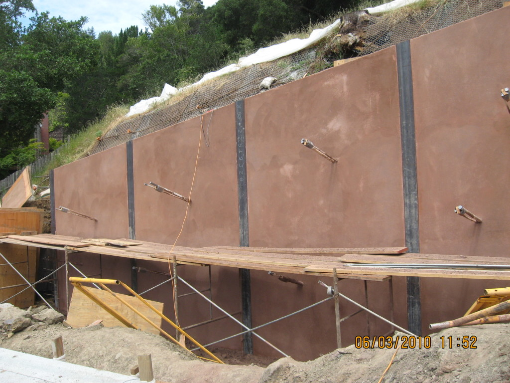 Steel soldier beam wall with colored shotcrete panels and tie-backs