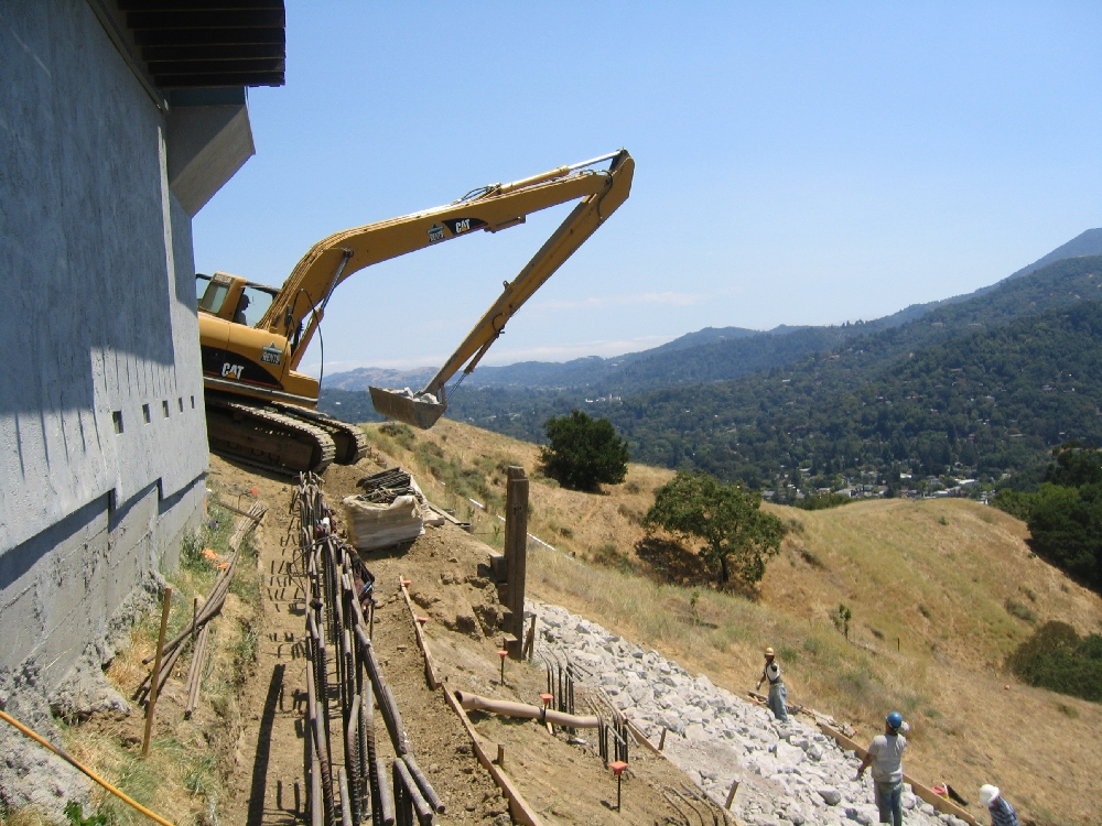 Installation of pier and gradebeam system to stabilize house foundation, and riprap to stabilize hillside.