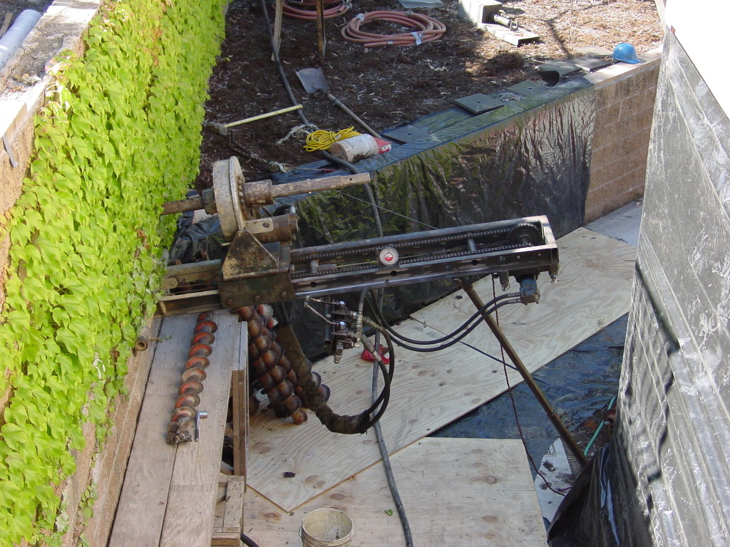 Drilling tieback for additional support for existing retaining wall
