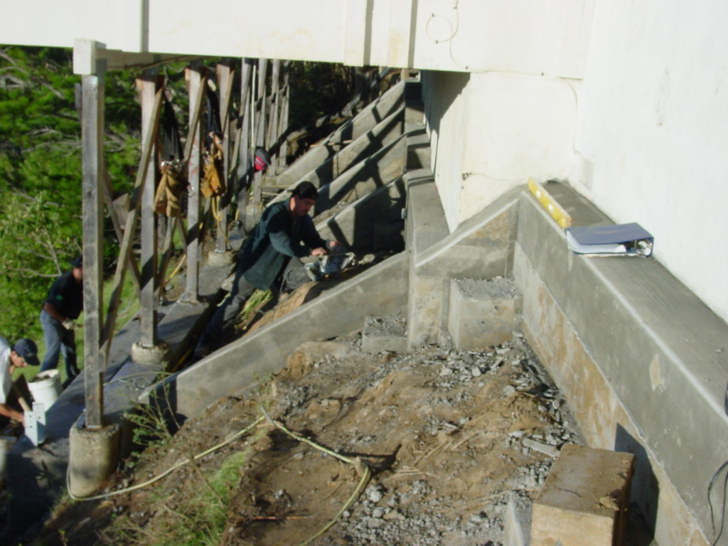 Underpinned house and deck foundations on hillside, with drilled, cast-in-place piers and gradebeams.