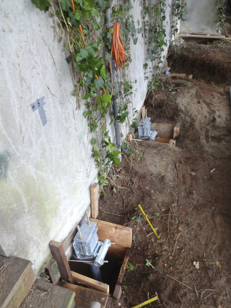 Underpinning of existing foundation with helical anchors; top brackets showing.
