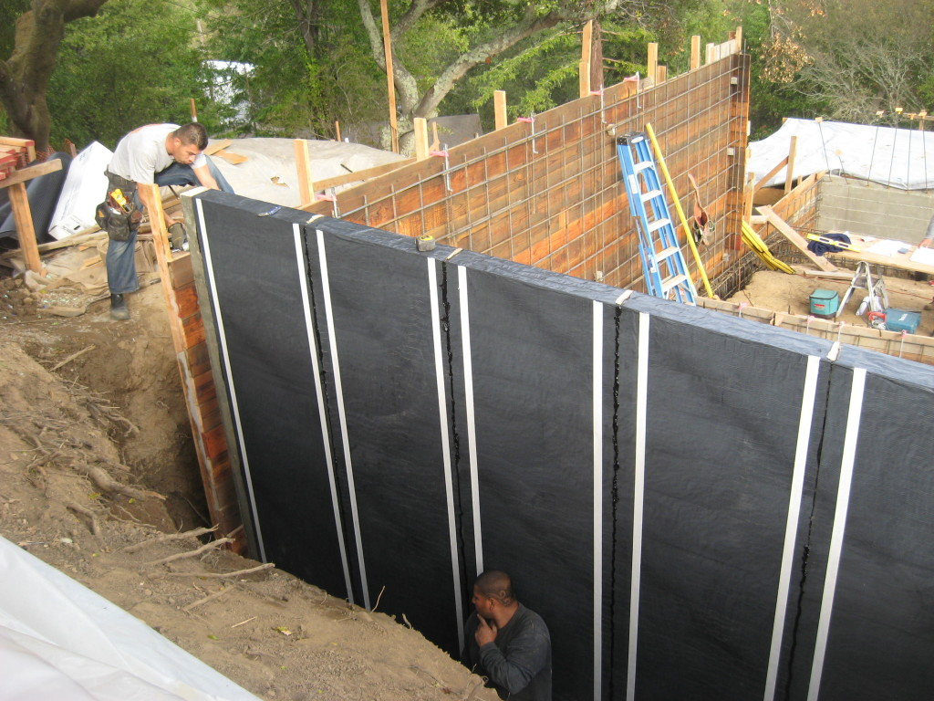 Waterproofing being applied to foundation wall